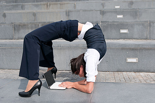 Business women bending backwards whilst typing on laptop